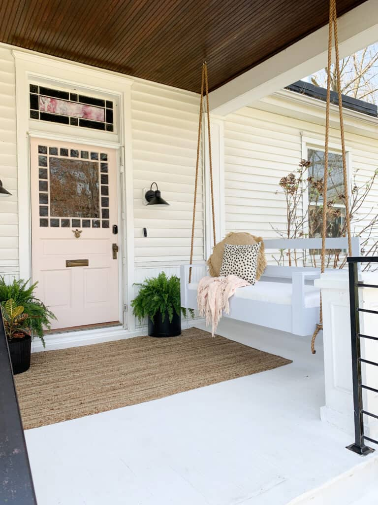 front porch with porch swing and pink door