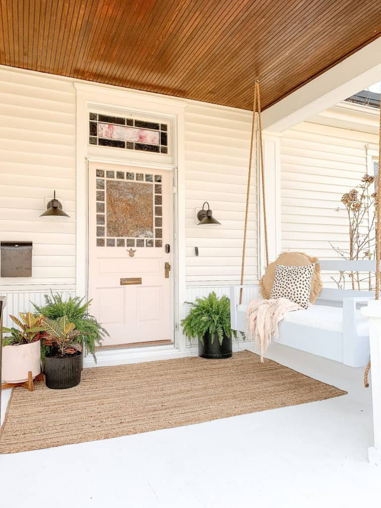 pink door on porch with porch swing