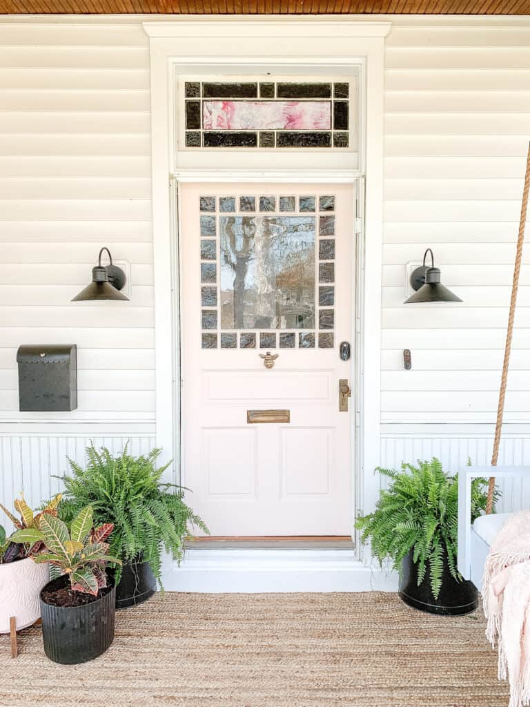 pink front door on house with black planters