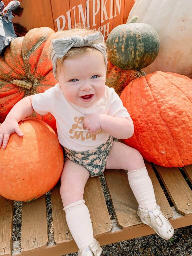 1 Year old girl sitting in pumpkins