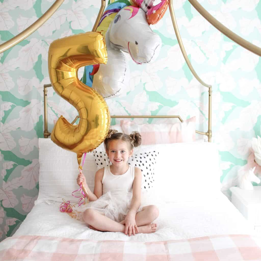 5 year old with 5 and unicorn balloon