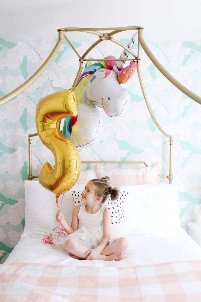 little girl on her bed with unicorn balloon
