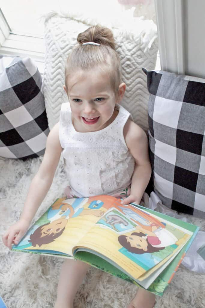 Toddler girl reading book