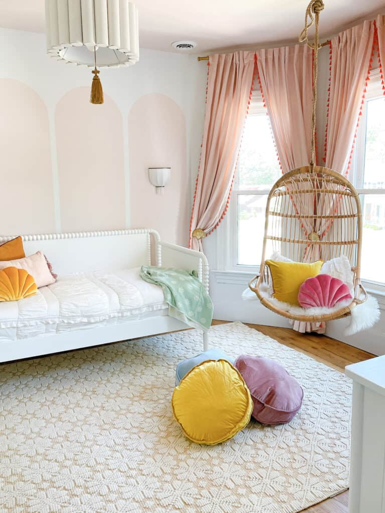 room with blush pink arches and hanging chair