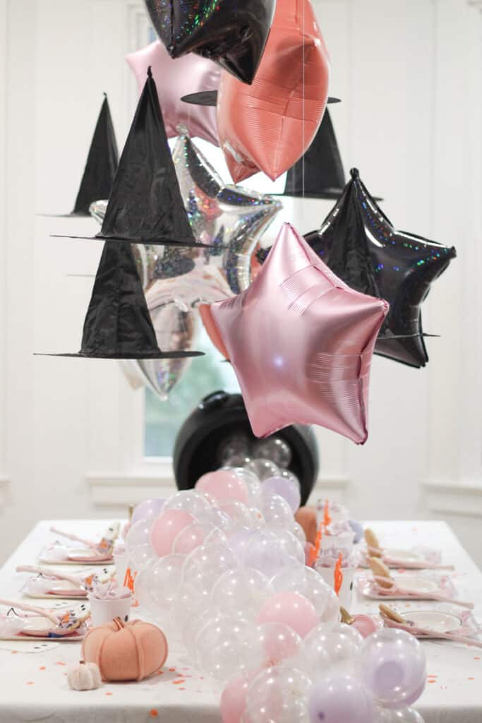 Pink stars and witch hats over table